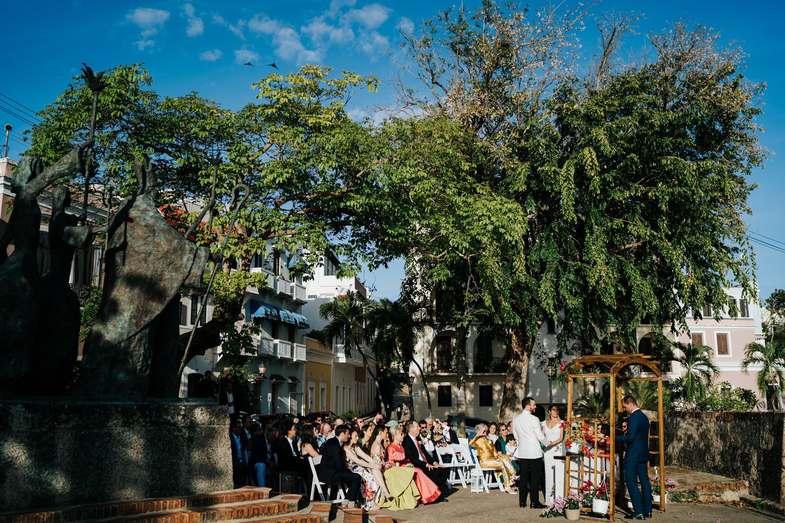Wide photograph of where the wedding ceremony took place at La Rogativa in Old San Juan, Puerto Rico with a beautiful, sun-lit tree in the background and guests at the front