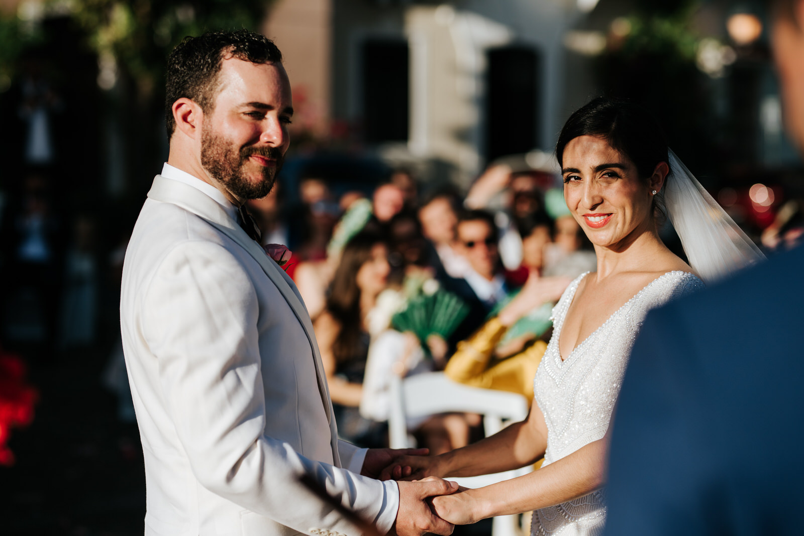 Close-up photograph of bride and groom holding hands and smiling at their officiant as he conducts the wedding ceremony