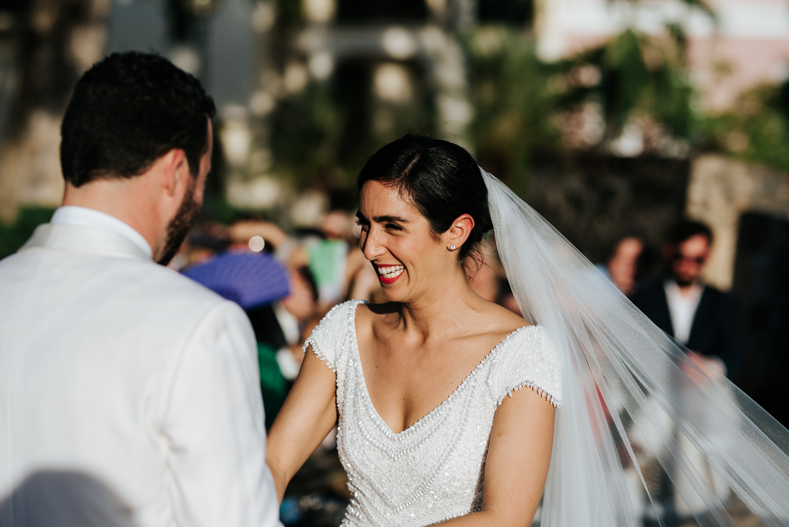 Bride cannot contain her laughter while holding hands with groom