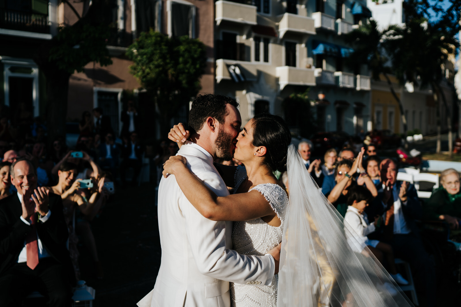 Bride and groom exchange their first kiss as husband and wife during their wedding ceremon with beautiful sunshine weather