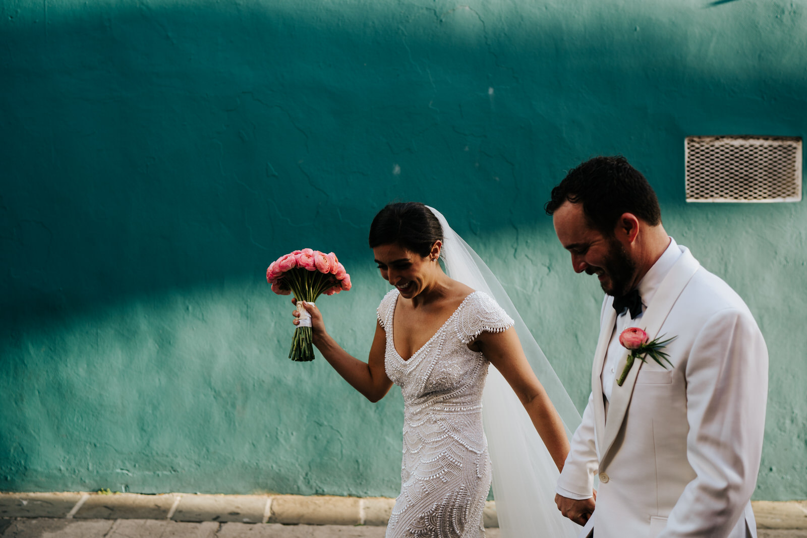 Bride and groom hold hands as they walk in front of turquoise wall in Old San Juan Puerto Rico