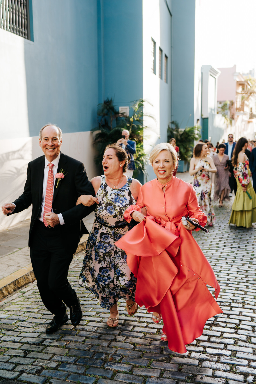 Groom's parents and a friend seen dancing and smiling as they walk towards the El Convento for the wedding reception
