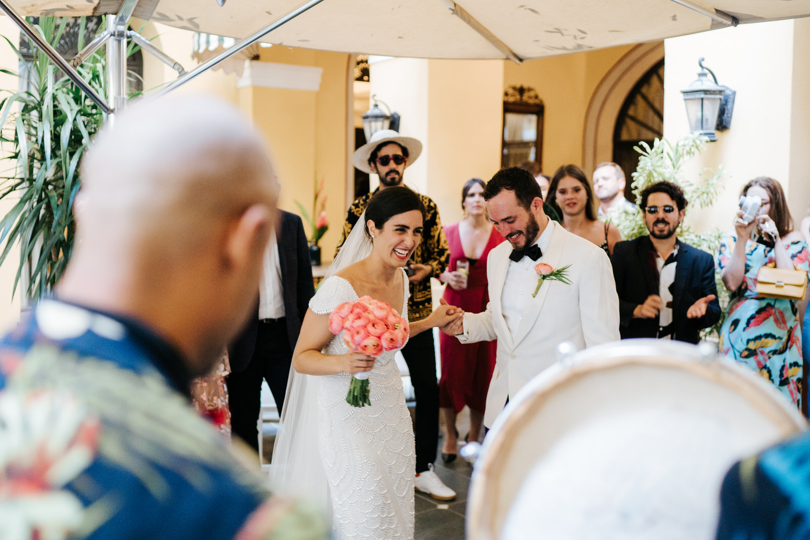Musicians are playing in the hotel's courtyard as bride and groom hold hands and smile, surrounded by guests