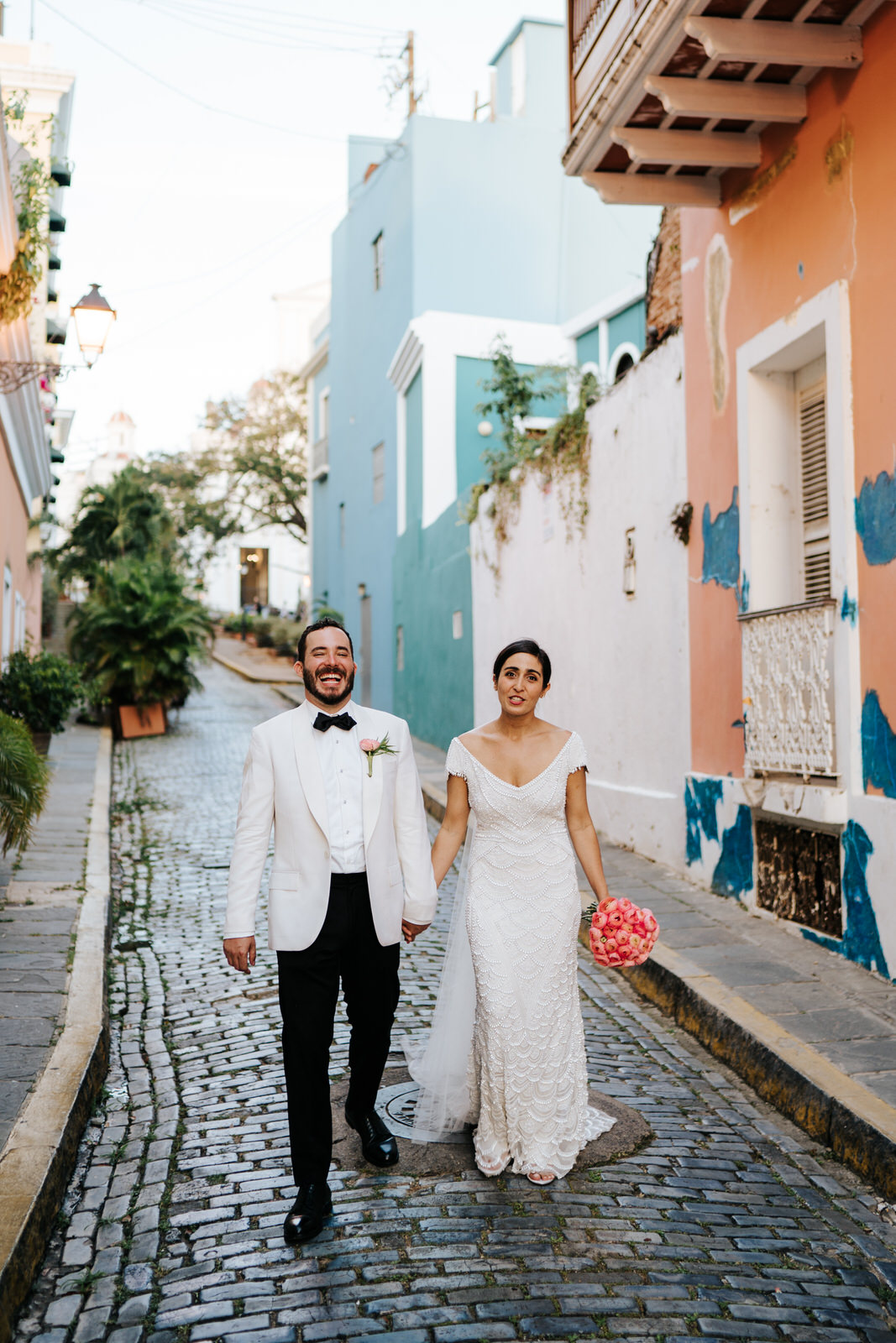 Bride and groom walk down the streets of Old San Juan while groom cannot contain his laughter and bride looks funnily at photographr