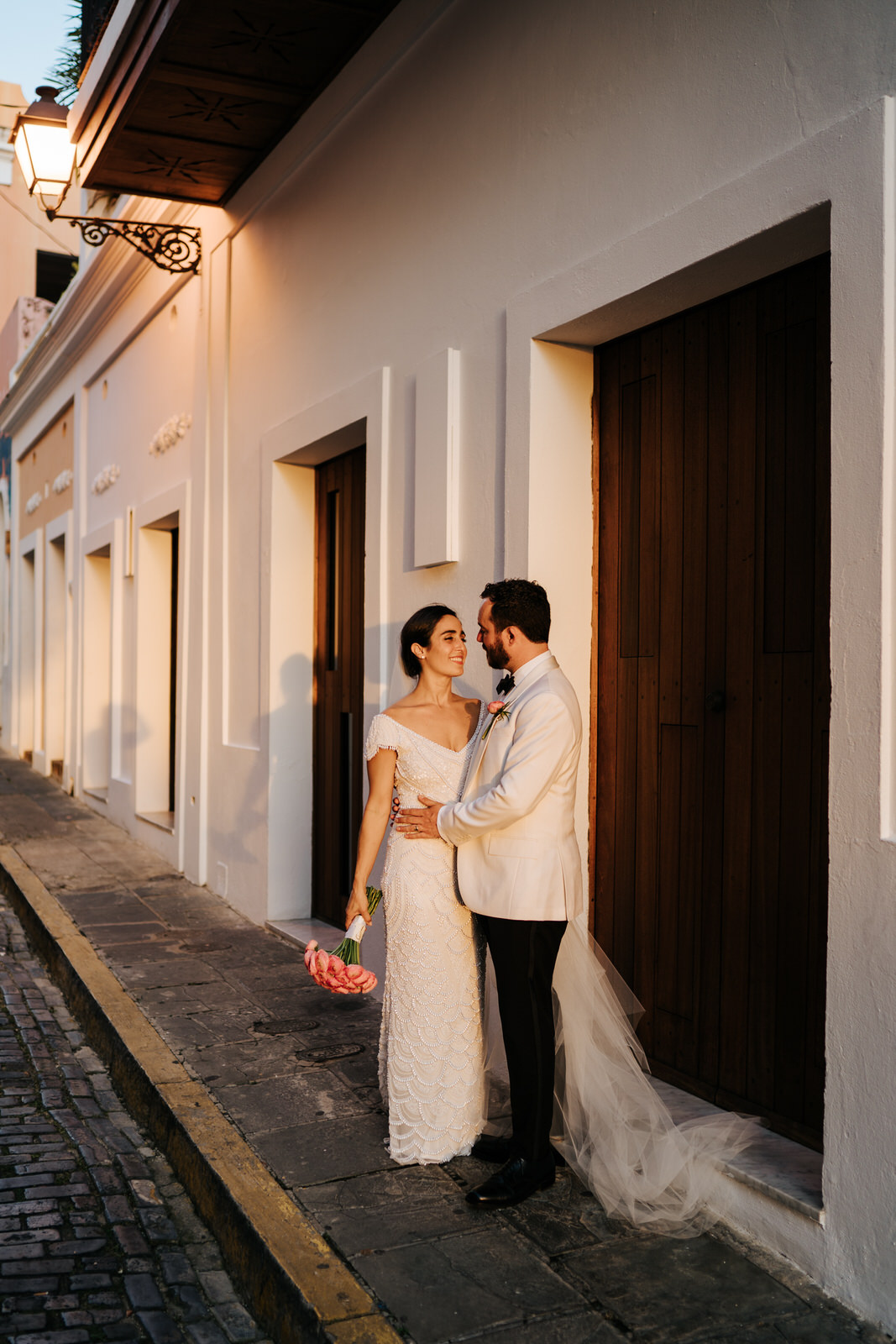 Beautiful, warm light shines on bride and groom as the sun sets in front of them and they embrace in the streets of Old San Juan