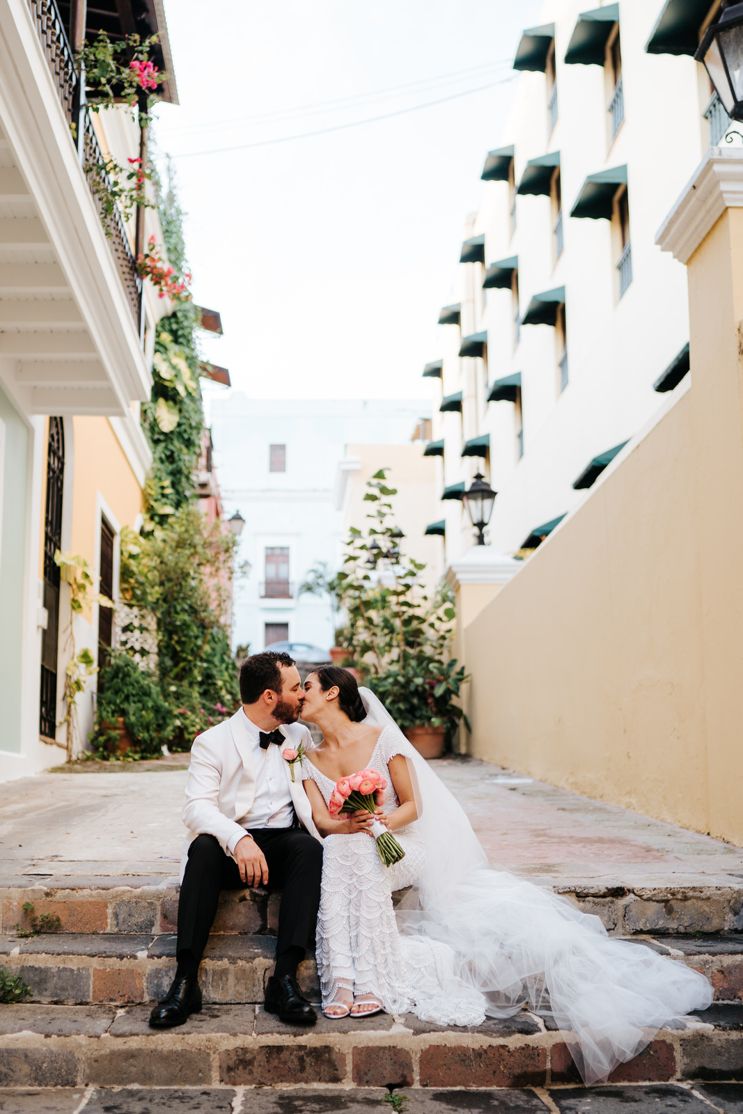 Bride and groom sit on cobblestone steps in an alley in Old San Juan while they kiss