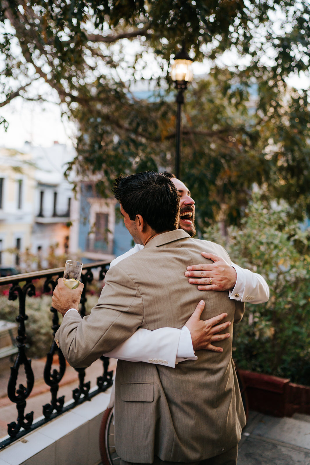 Groom has an outburst of joy and hugs a friend as he returns to the hotel El Covento for the wedding reception