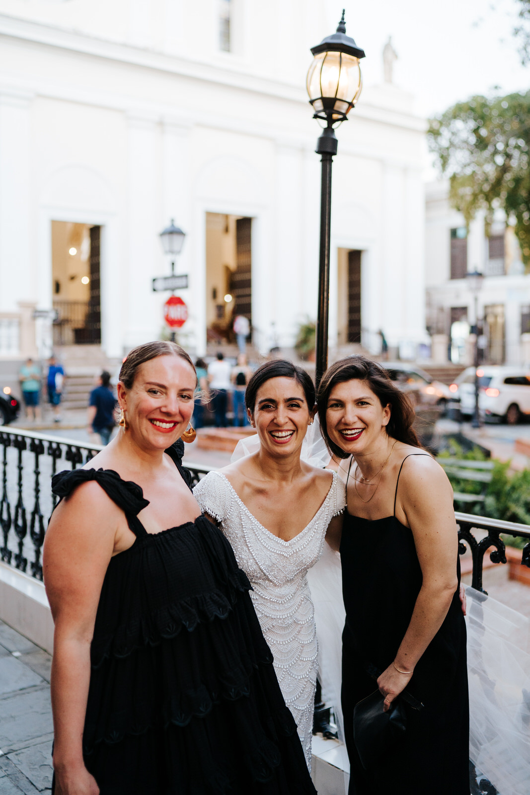 Group photograph of bride and two of her friends posing for a photo and looking at the camera