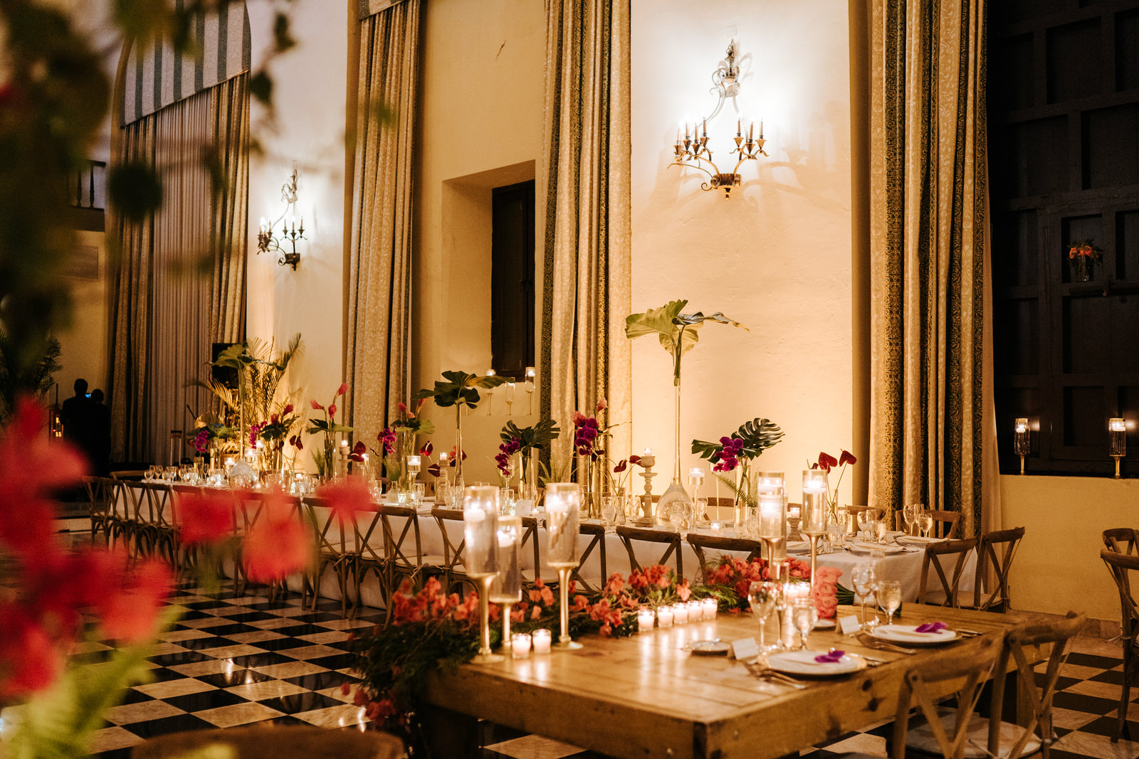 Wide photograph of the decoration in the Hotel El Convento wedding room accentuated with green leaves and red flowers