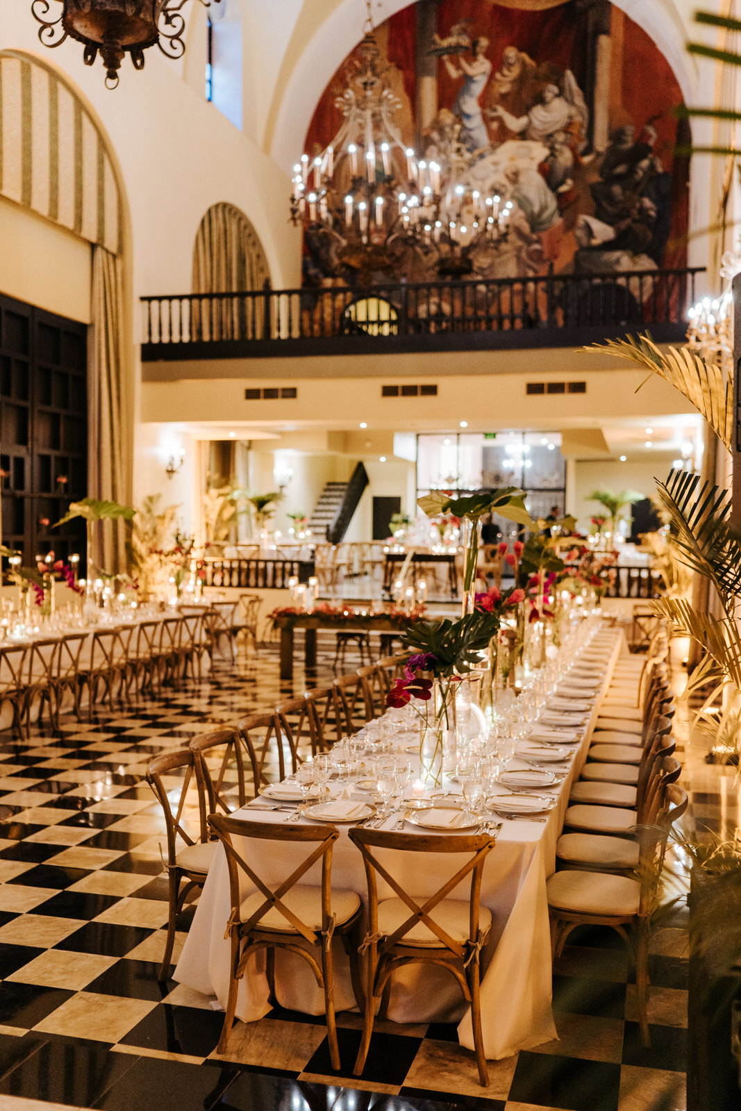 Wide vertical photograph of the decoration in the Hotel El Convento wedding room accentuated with green leaves and red flowers
