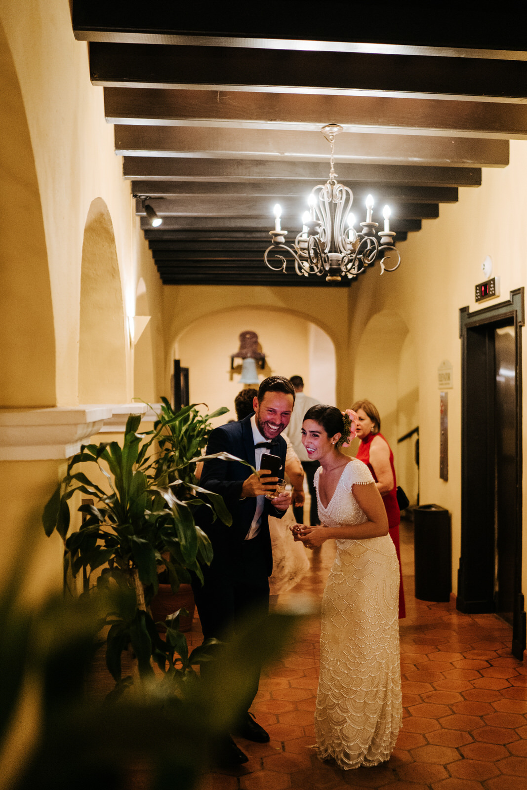 Bride stands in the hallway of the wedding venue as a friend shows her a photo on his phone and they both smile