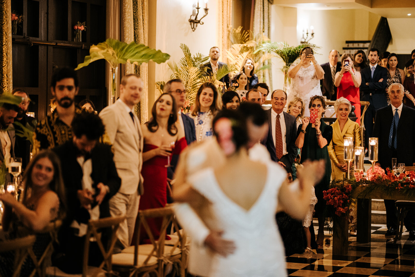 Bride and groom during their first dance, out of focus, while everyone in the background smiles at them and some guests take photos