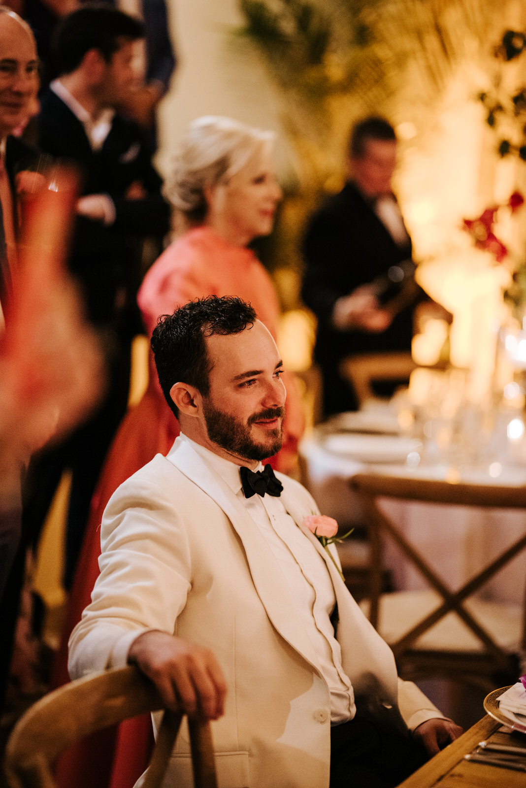 Groom sits and watches on as bride dances with his father in emotional dance