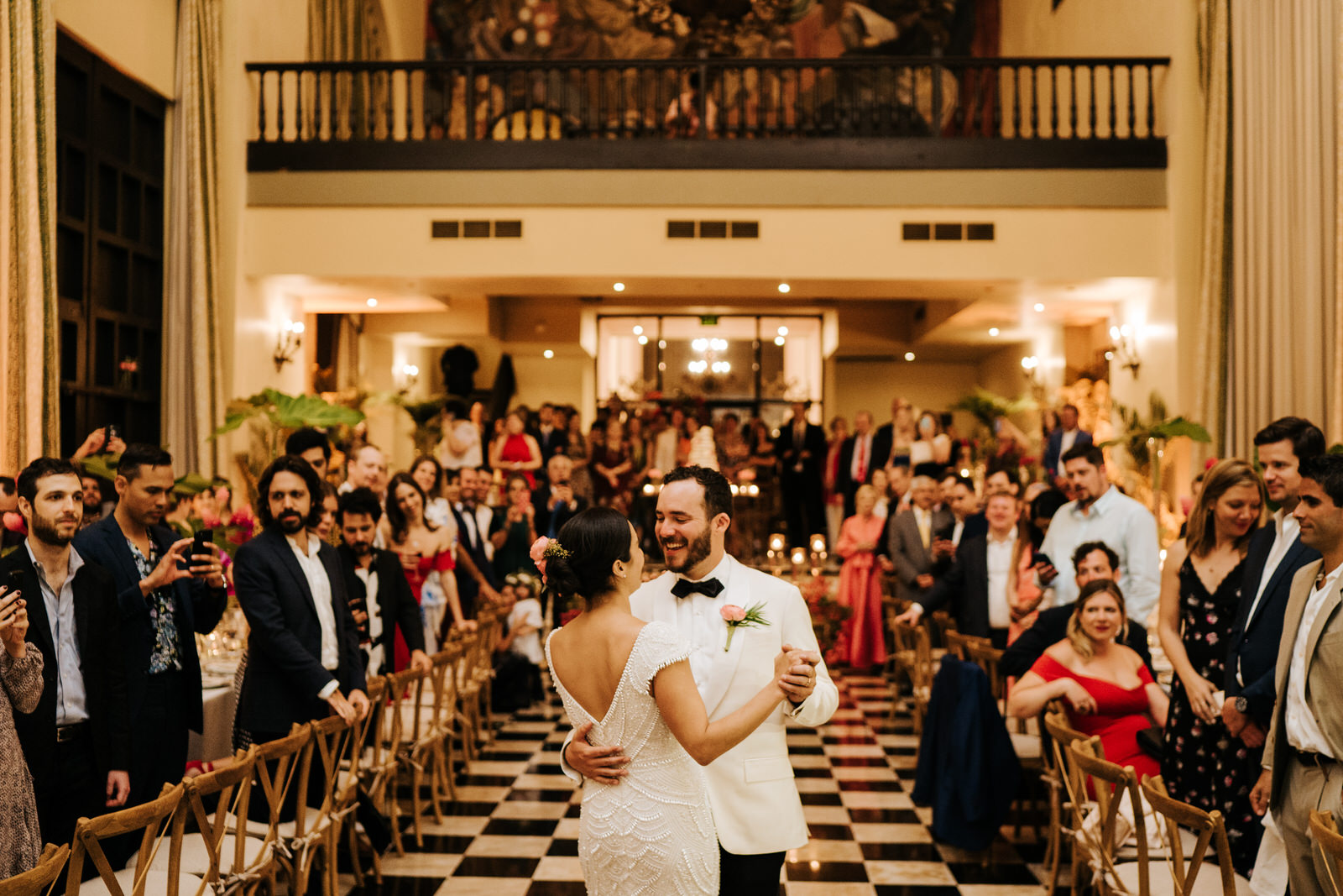 Wide photograph of bride and groom having their first dance. Bride's back is towards the camera while groom smiles at her.