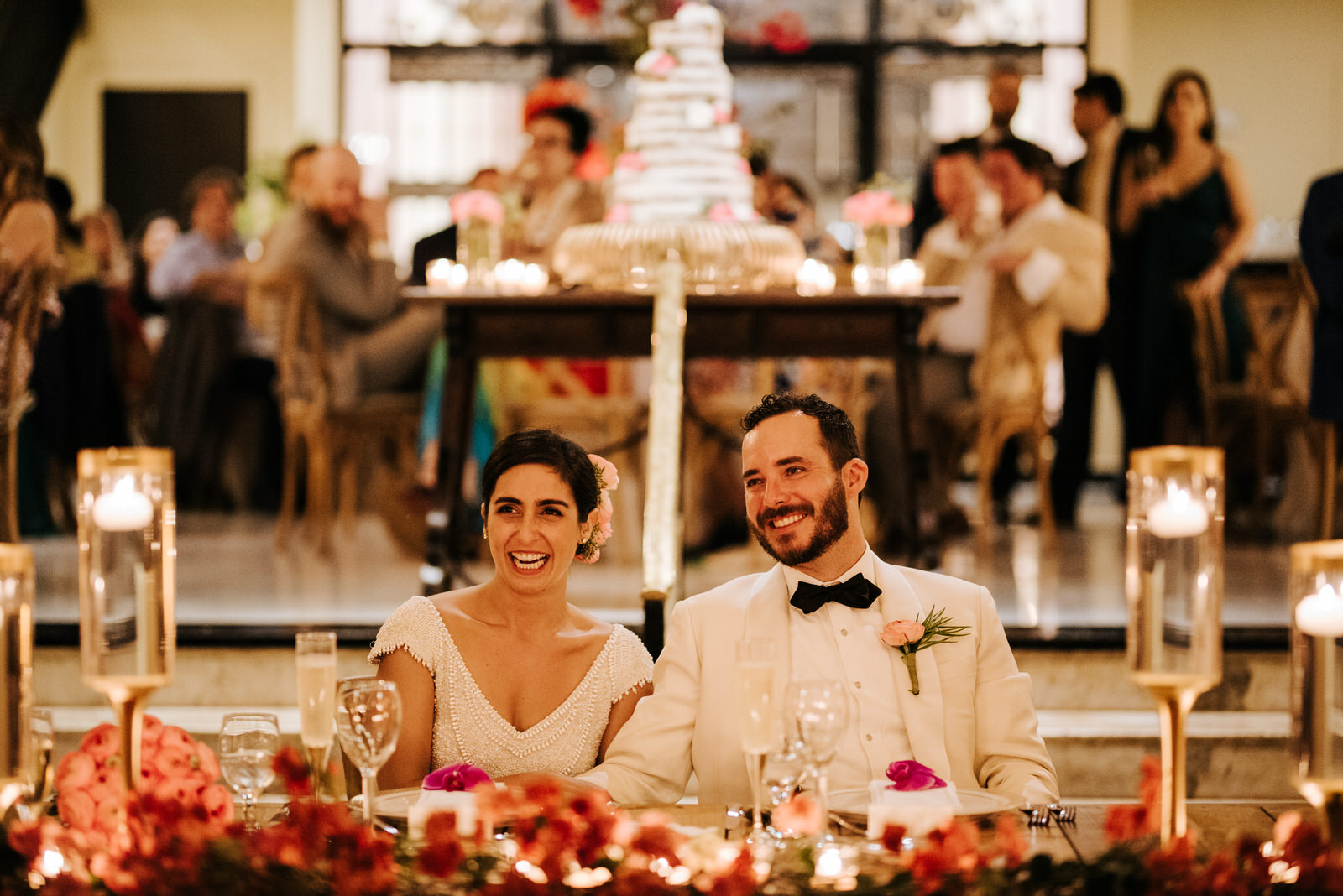 Bride and groom are sitting at their wedding table and smile during the speeches