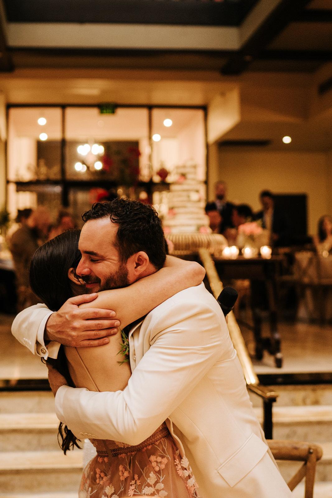 Groom hugs bride's best friend after she finishes her wedding speech