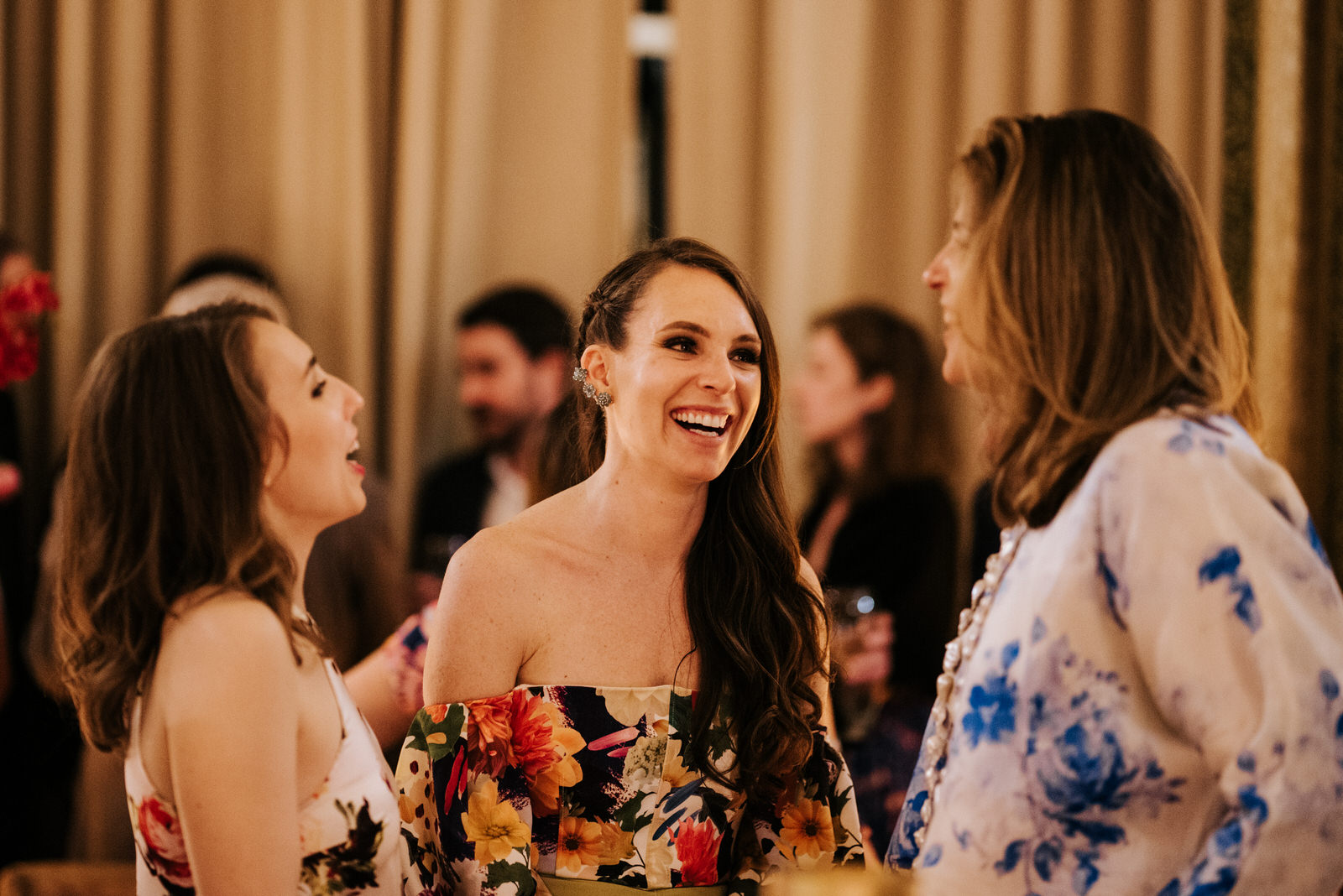 Candid photograph of groom's sisters talking to a friend and smiling