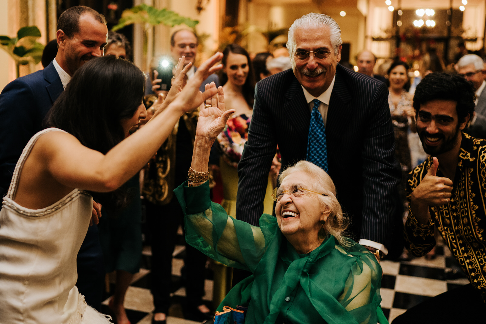 Bride's grandmother is on the dancefloor in her wheelchair and smiling as everyone encourages her and bride smiles at her