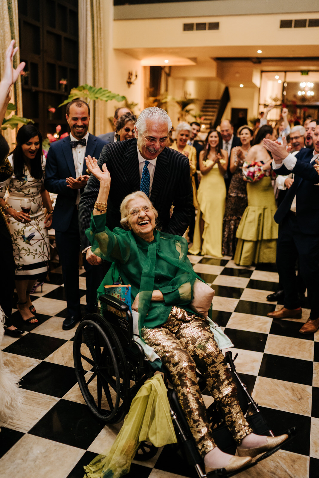 Bride's grandmother is on the dancefloor in her wheelchair and smiling as everyone encourages her and she waves
