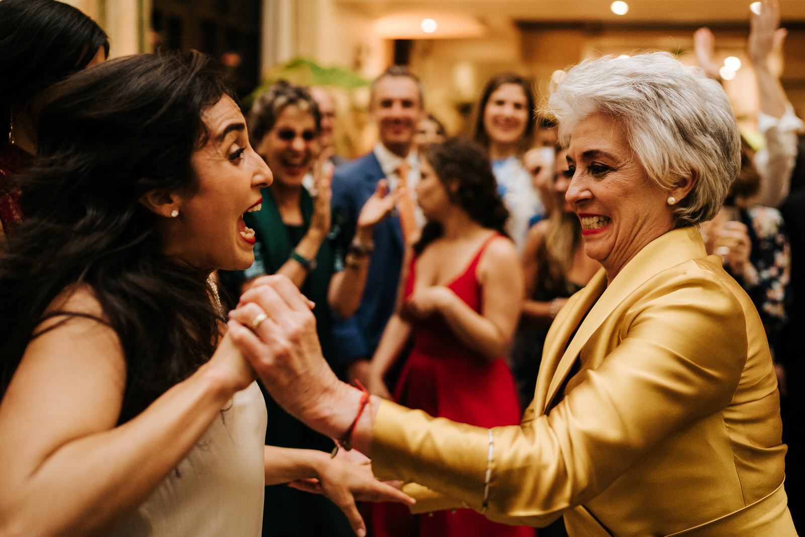 Bride and her mother having a fantastic time as they hold hands and dance on the dancefloor