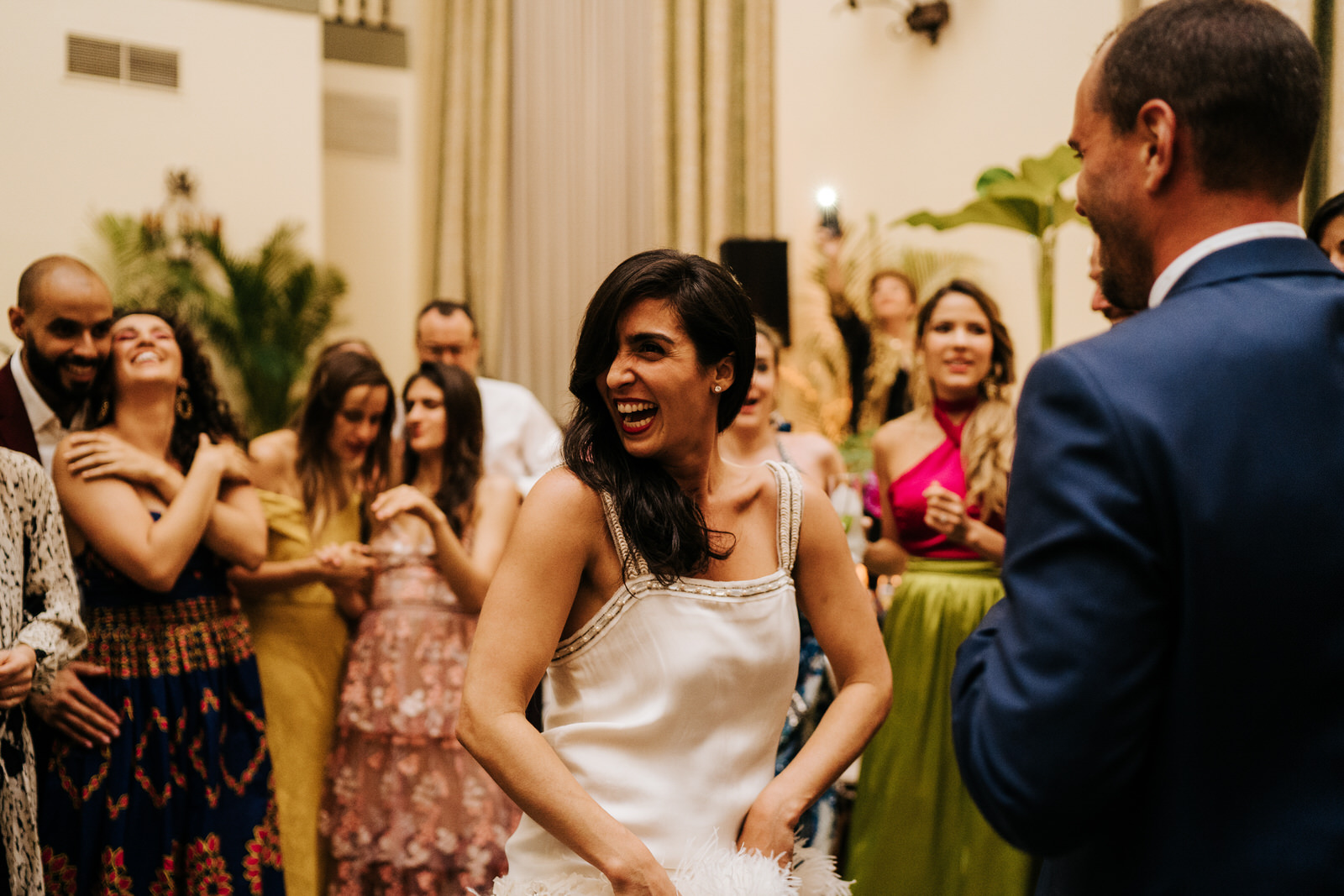 Bride smiles and cheers as she dances on the dancefloor