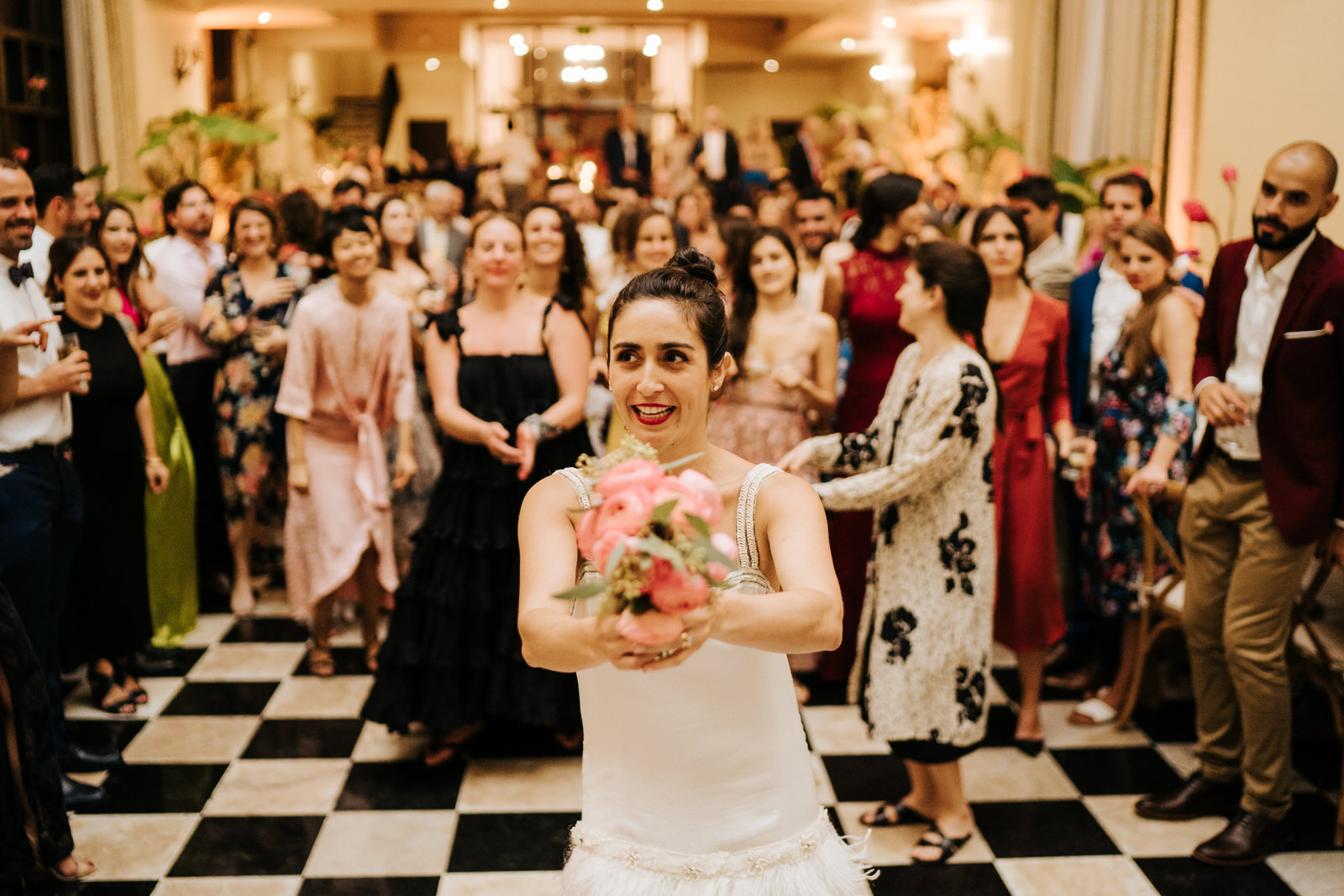 Bride holds her bouquet as her female friends stand behind her ready to catch it