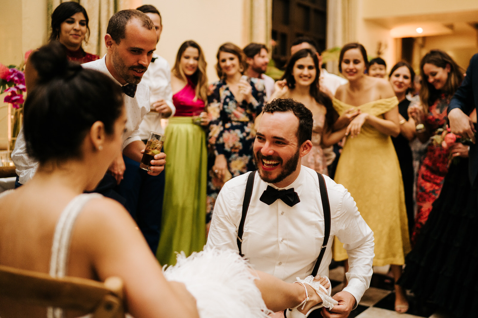 Groom smiles as he takes off the bride's garter as she sits on a chair