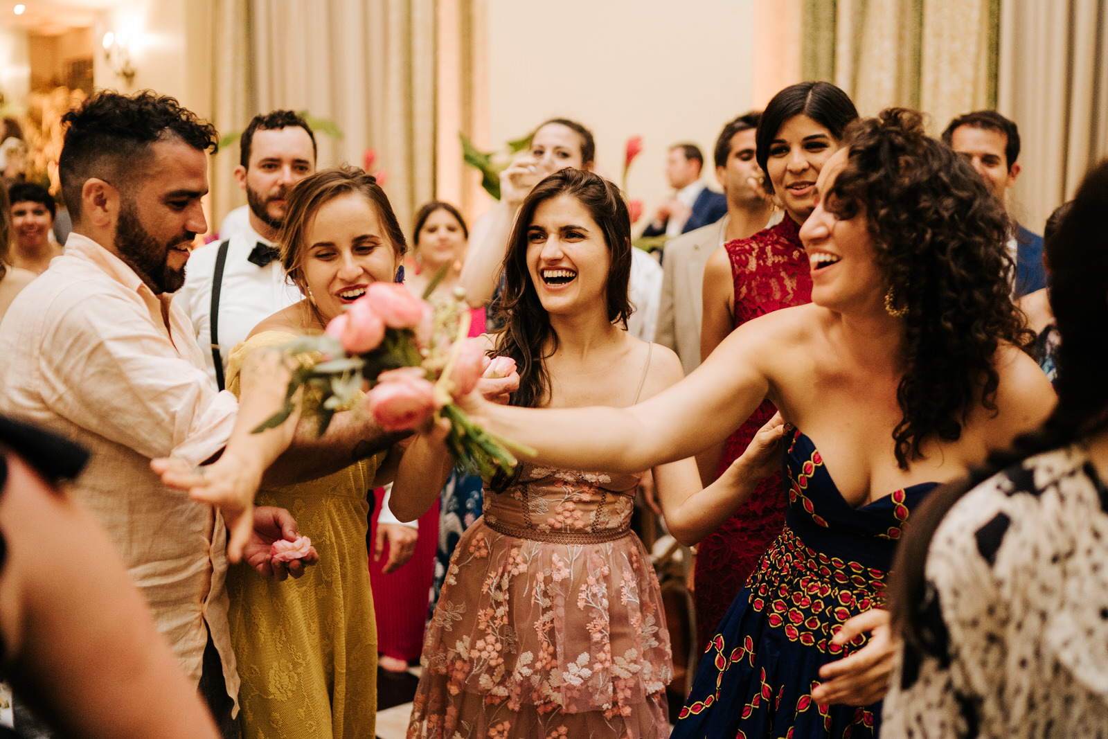 Photograph of the person who caught the bouquet and other friends laughing alongside her