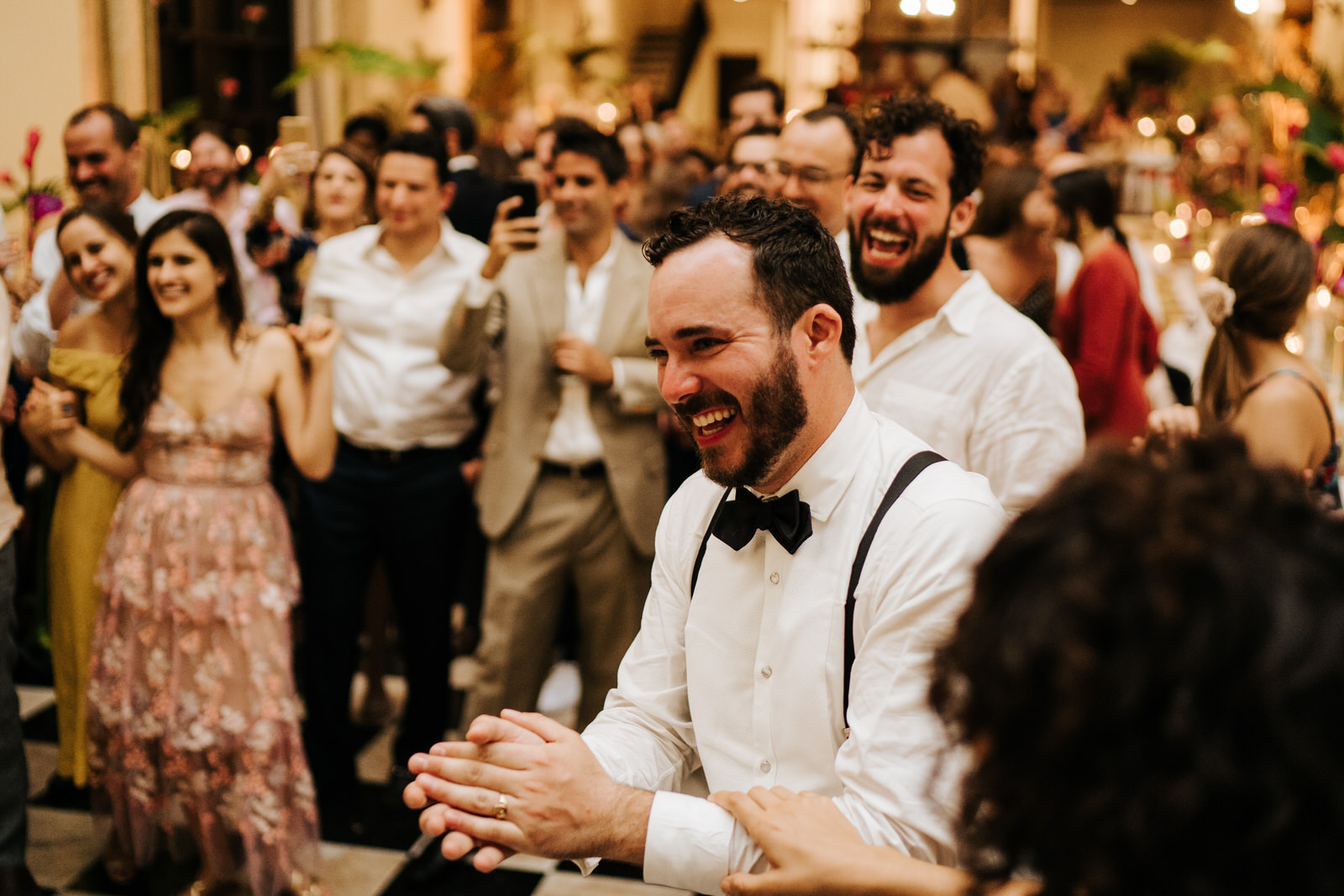 Groom laughs and claps his hands as he reacts to the friend who took the microphone