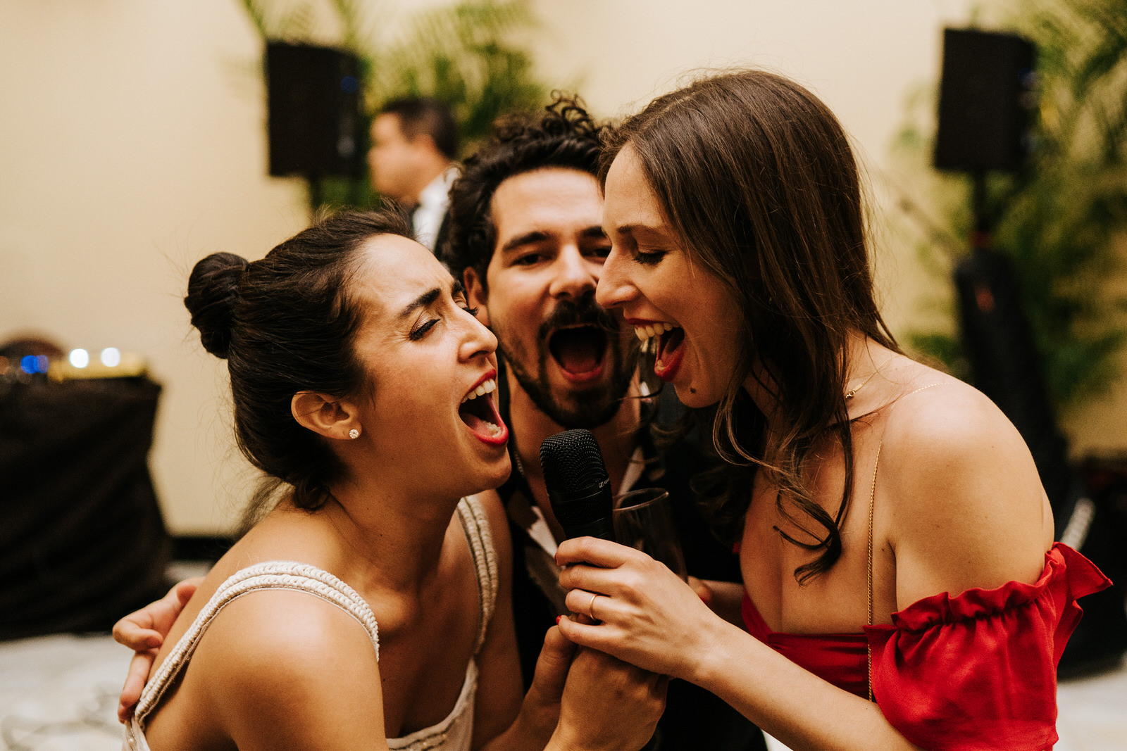 Bride and two friends hold the microphone and sing into it passionately