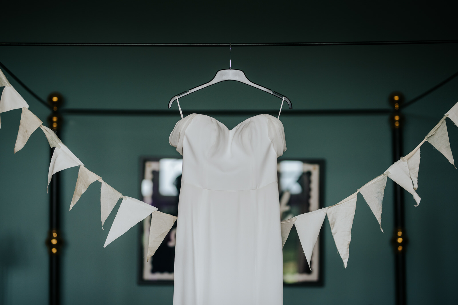Bride's dressing hanging by bed in dressing room
