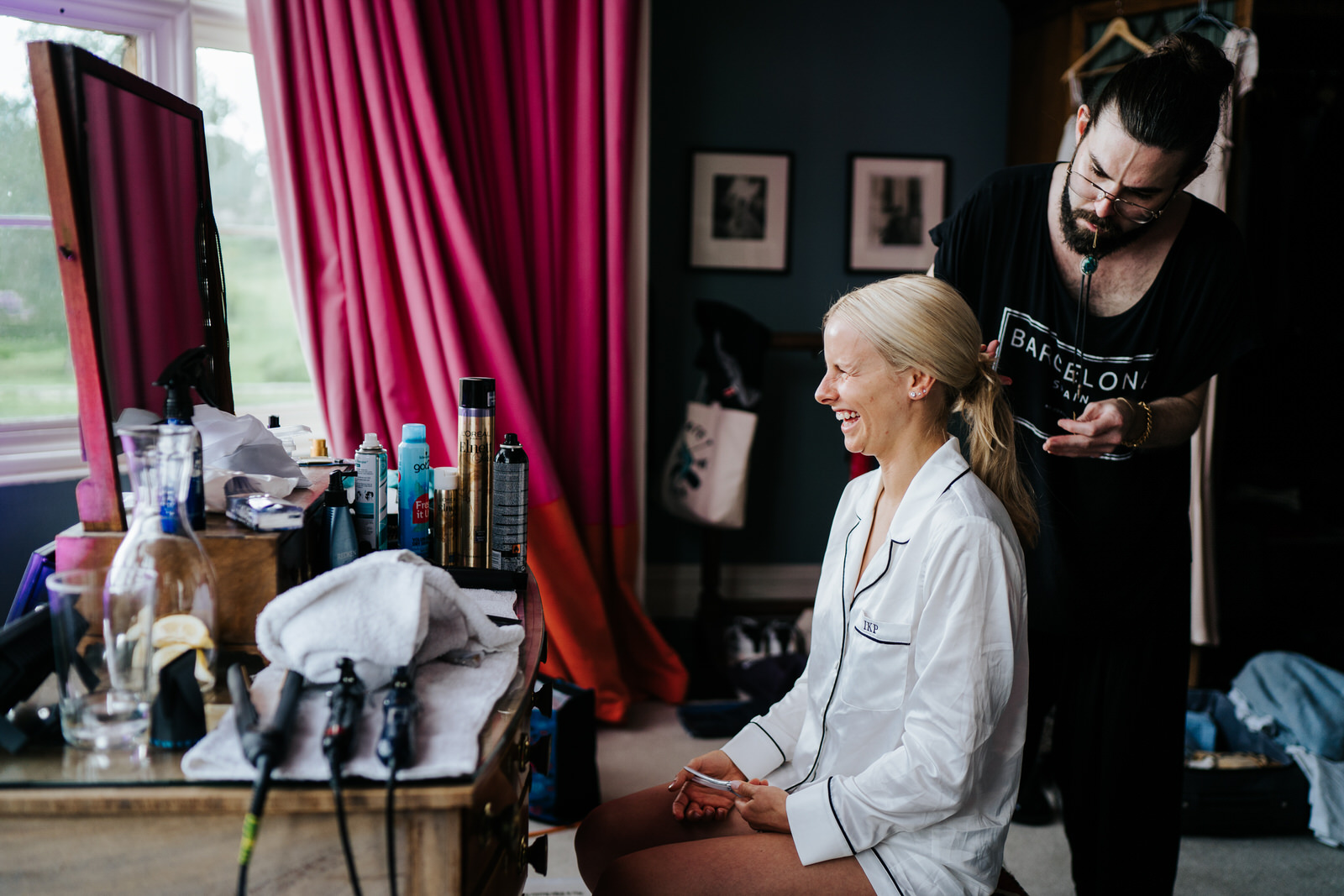 Bride sitting and smiling in front of mirror while makeup artist works on her hair