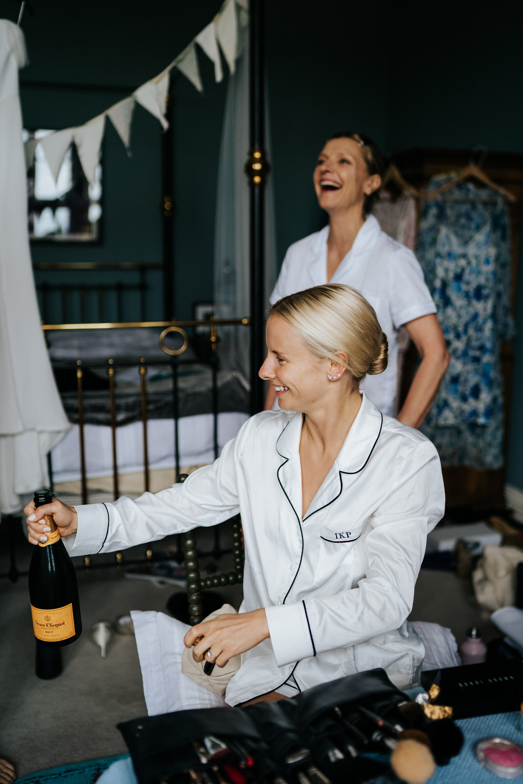 Bride holds and opens a bottle of champagne while mother of the bride smiles in the background