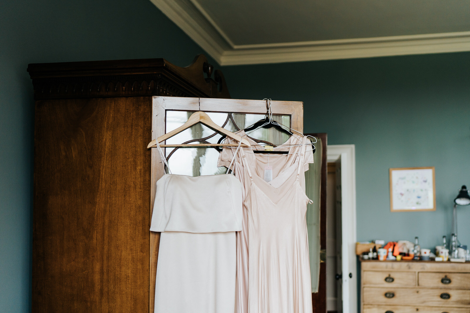 Bridesmaid dresses hang on the door of a closet in dressing room