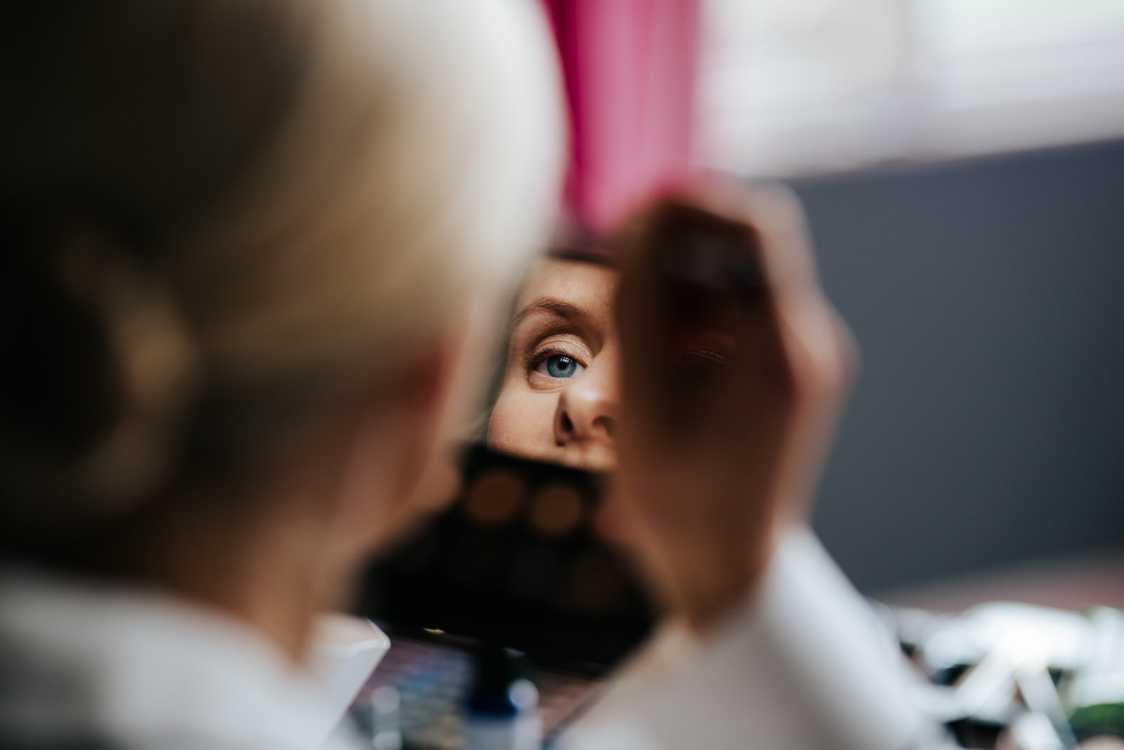 Bride's eye reflected in a small mirror as she focusedly applies makeup to her eyebrows