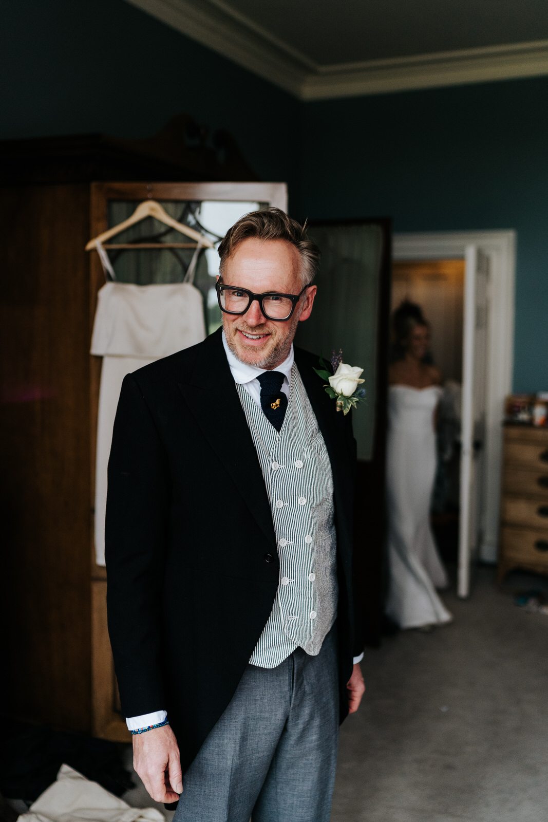 Father of the bride looks excitedly at the camera while the bride, fully dressed in her gown, enters at the back
