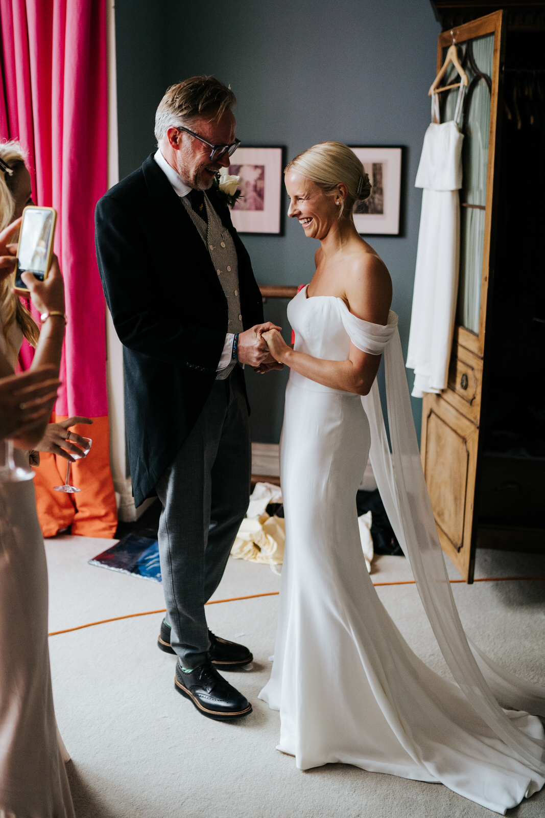 Father of the bride and bride hold hands as he sees her in her dress for the first time