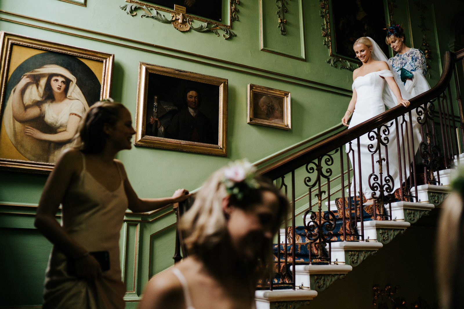 bride, two sisters and mother of the bride walk down the stairs at Hawarden Castle Wedding