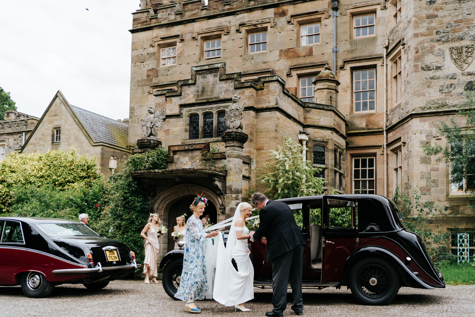 Bride, mother of the bride and bridesmaids stand against majestic Hawarden Castle venue as bride enters her wedding car