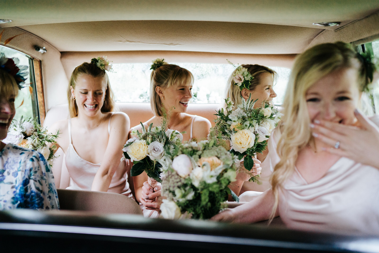 Bridesmaids and mother of the bride sit in the back of the car and smile as they are driven to wedding ceremony