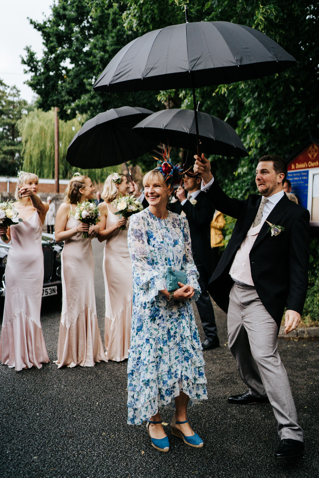 Mother of the bride and bridesmaids stand, smiling, underneath umbrellas as they wait for the bride to exit her car