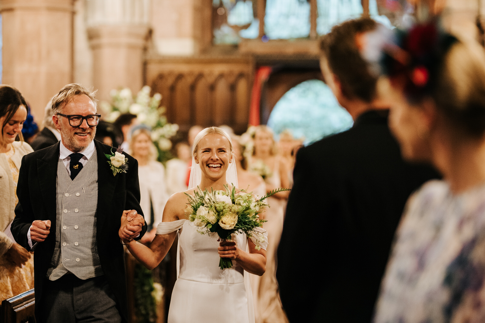 Father of the bride and bride walk down the aisle, holding hands and smiling vibrantly at Hawarden Castle Wedding