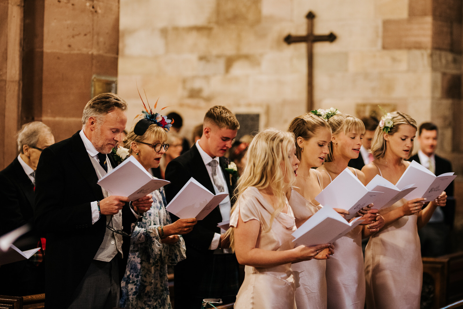 Bridesmaids and bride's side of the family all lined up in the pews singing a hymn