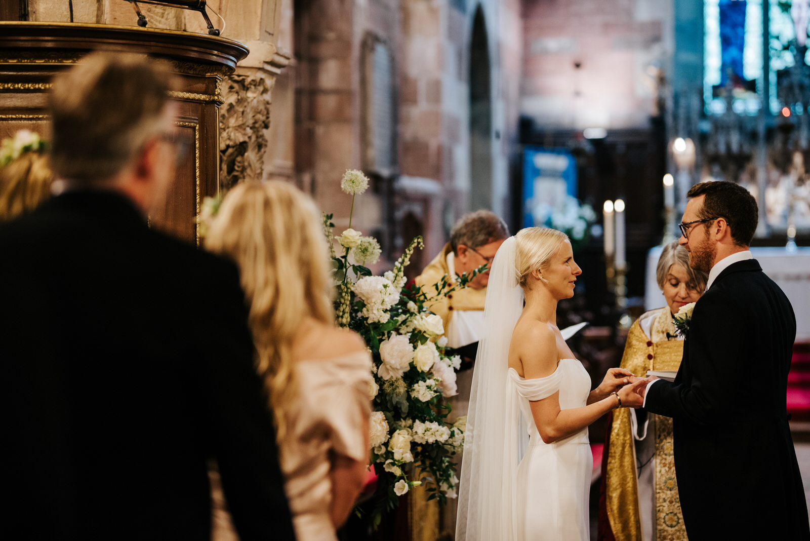 Bride and groom hold hands and exchange rings during wedding ceremony in Hawarden, Wales