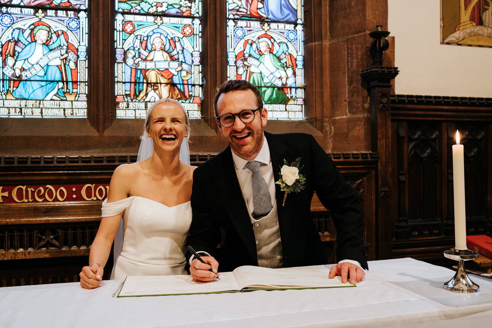 Bride and groom smile at camera while taking staged photograph of registry signing