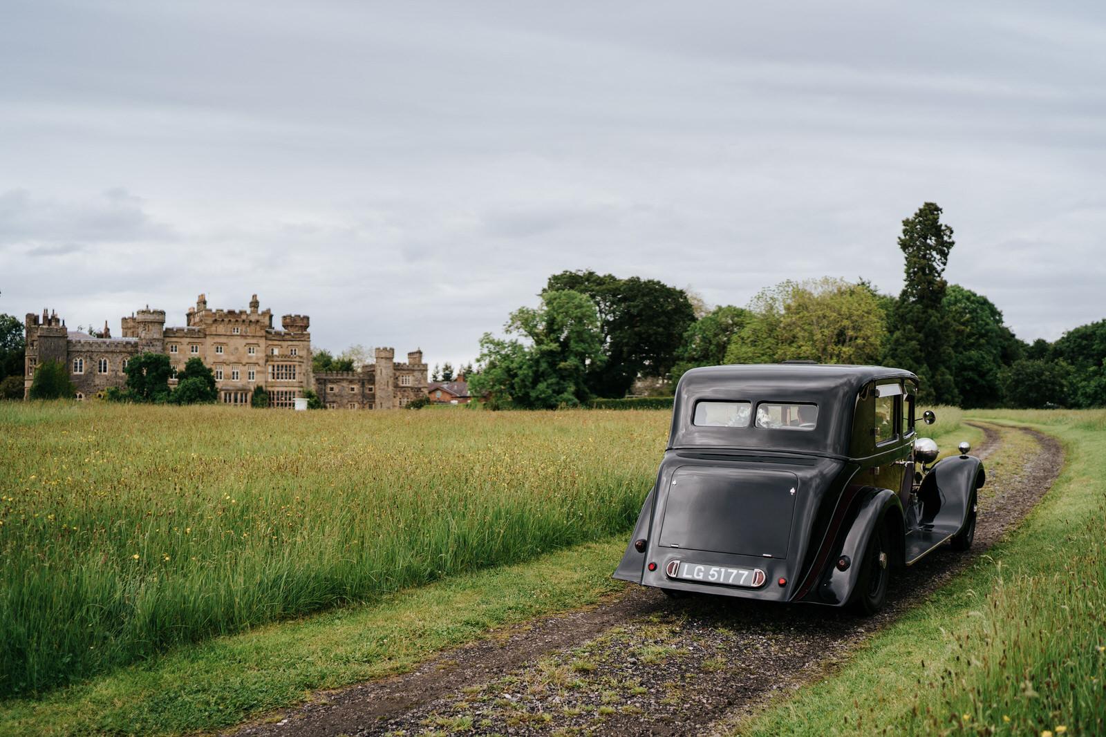 Bride and groom drive towards Hawarden Castle in beautiful, black vintage car