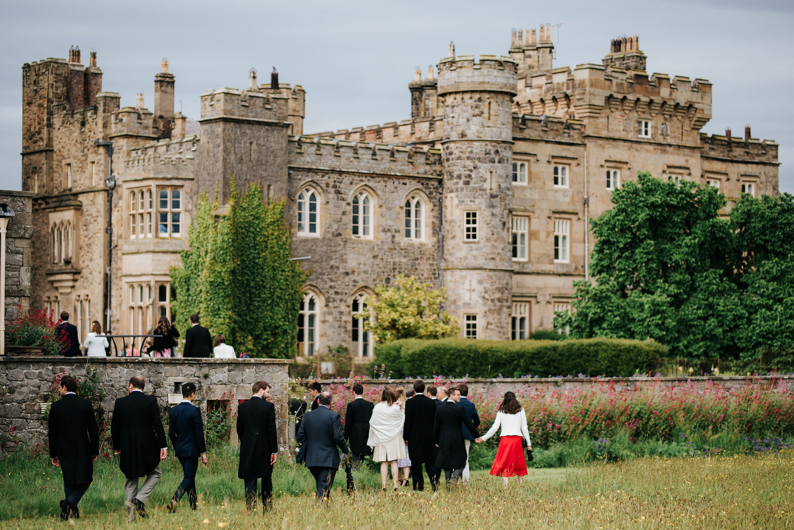 Guests and family walk across the lawn towards Hawarden Castle for the drinks reception