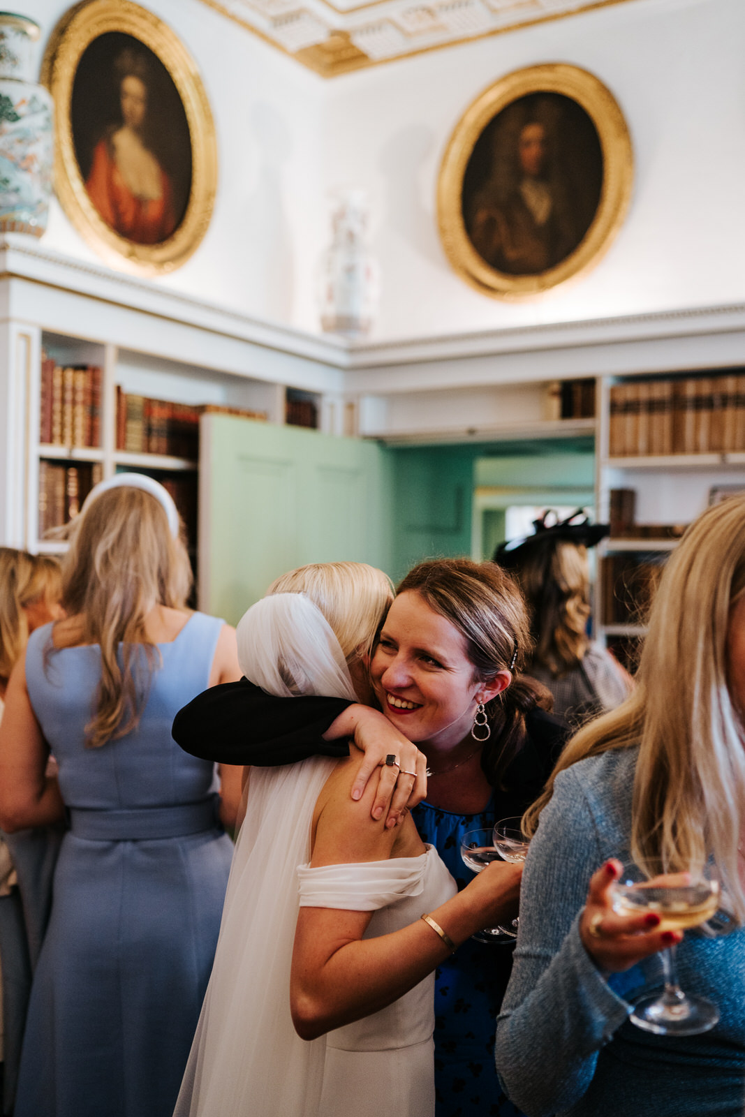 Bride hugs a friend during the champagne reception in historic Hawarden Castle