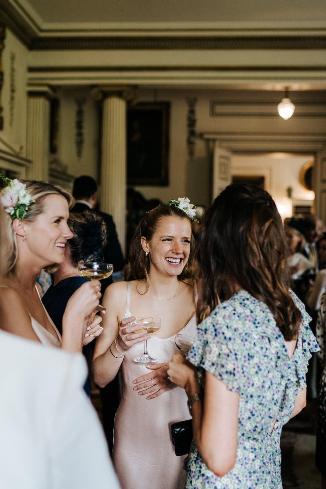 Bride's two sisters talk to a friend during the champagne reception
