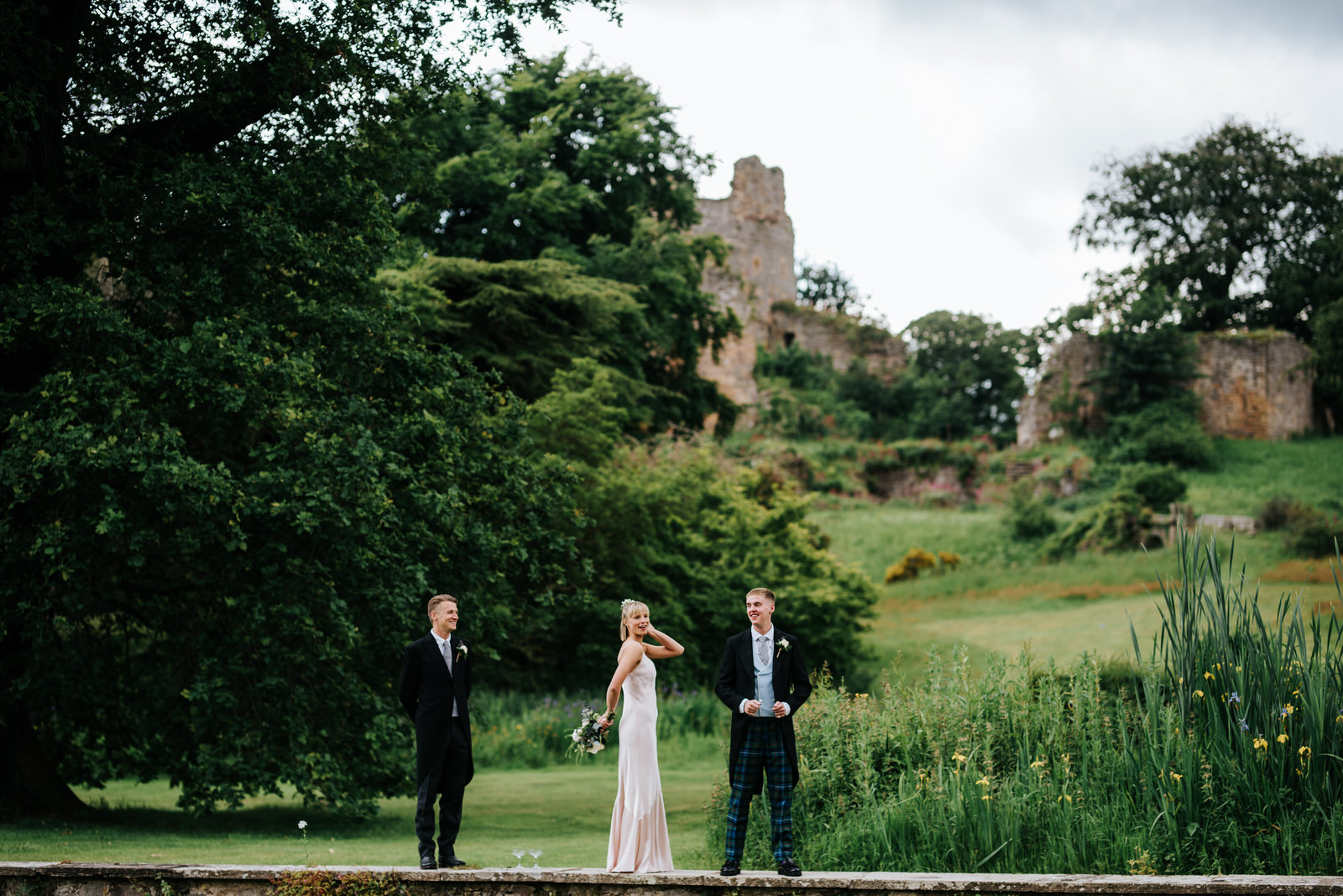 Bride's three siblings goof around outside Hawarden Castle